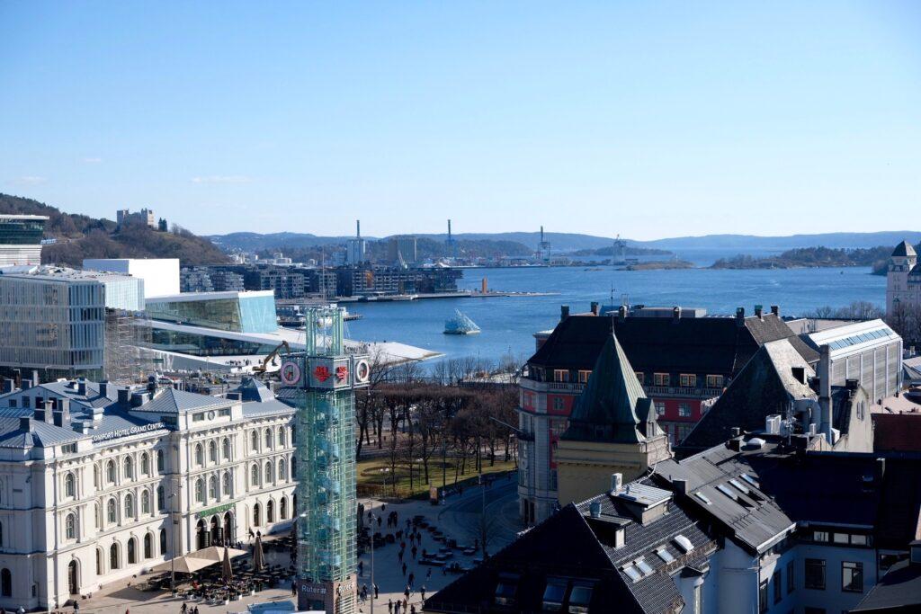 """Oslo sett från hustaket på The Hub. Ute på fjorden skymtas konstverket """"She Lies""""."""